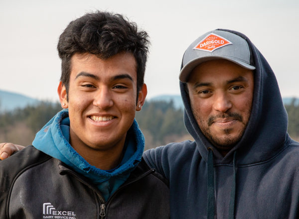 Two young men in sweaters smile for the camera
