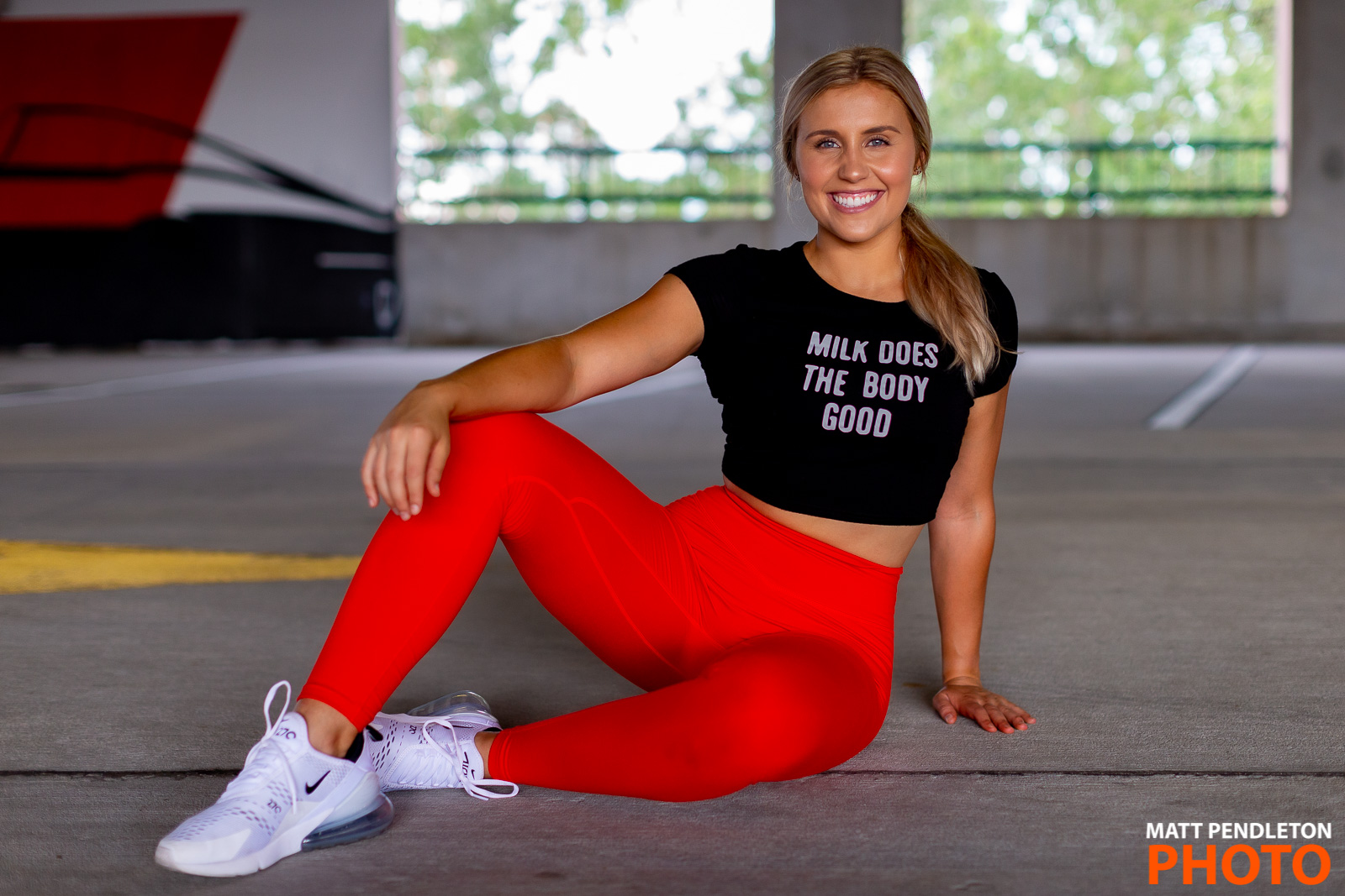 A blonde woman in a black shirt and red exercise pants poses for the camera
