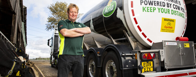 A man standing next to a milk truck poses for the camera