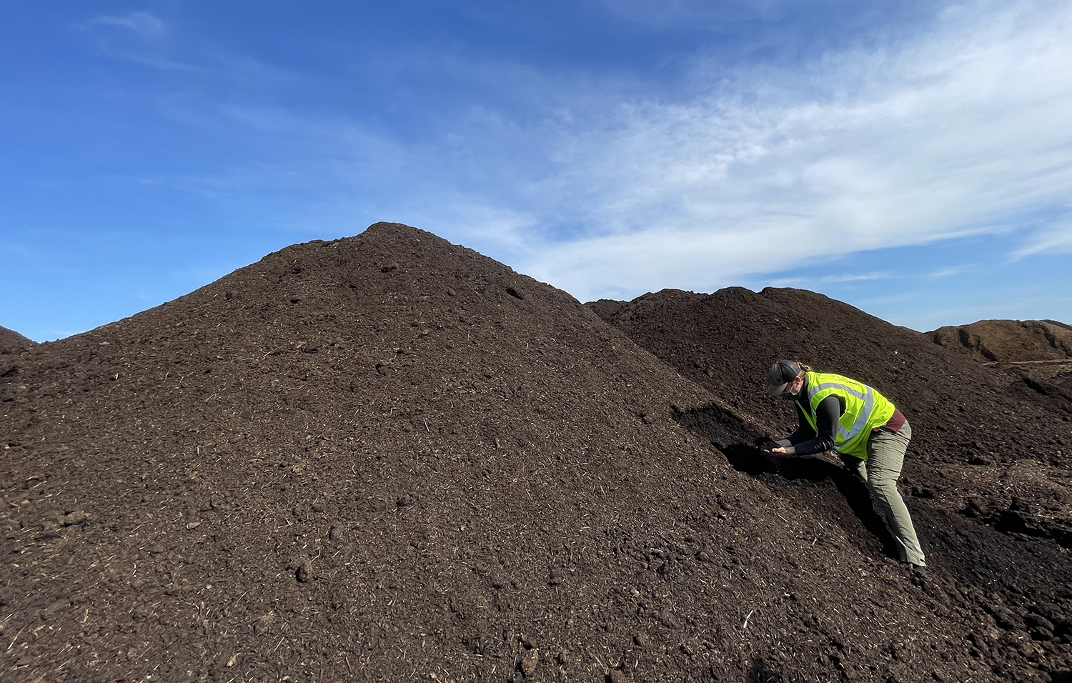 A large pile of compost against a bright blue sky and a man in a yellow jacket