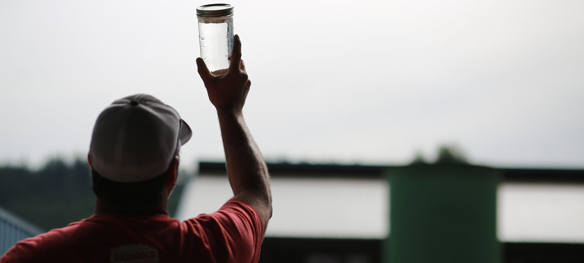 Man holding jar of clean water up to the sky