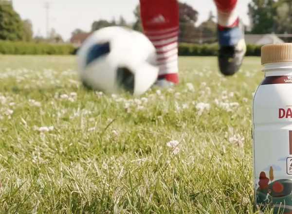 Someone with red soccer socks kicks the ball near a bottle of Darigold FIT