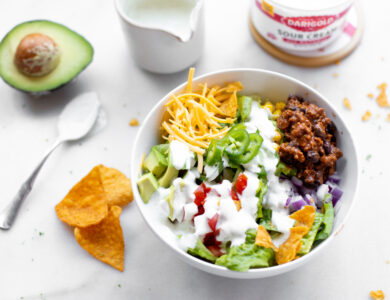 A bowl of taco salad, with chips, an avocado and sour cream