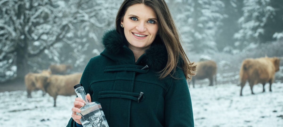 A woman with a black coat holds a bottle of clear liquor against a snowy backdrop