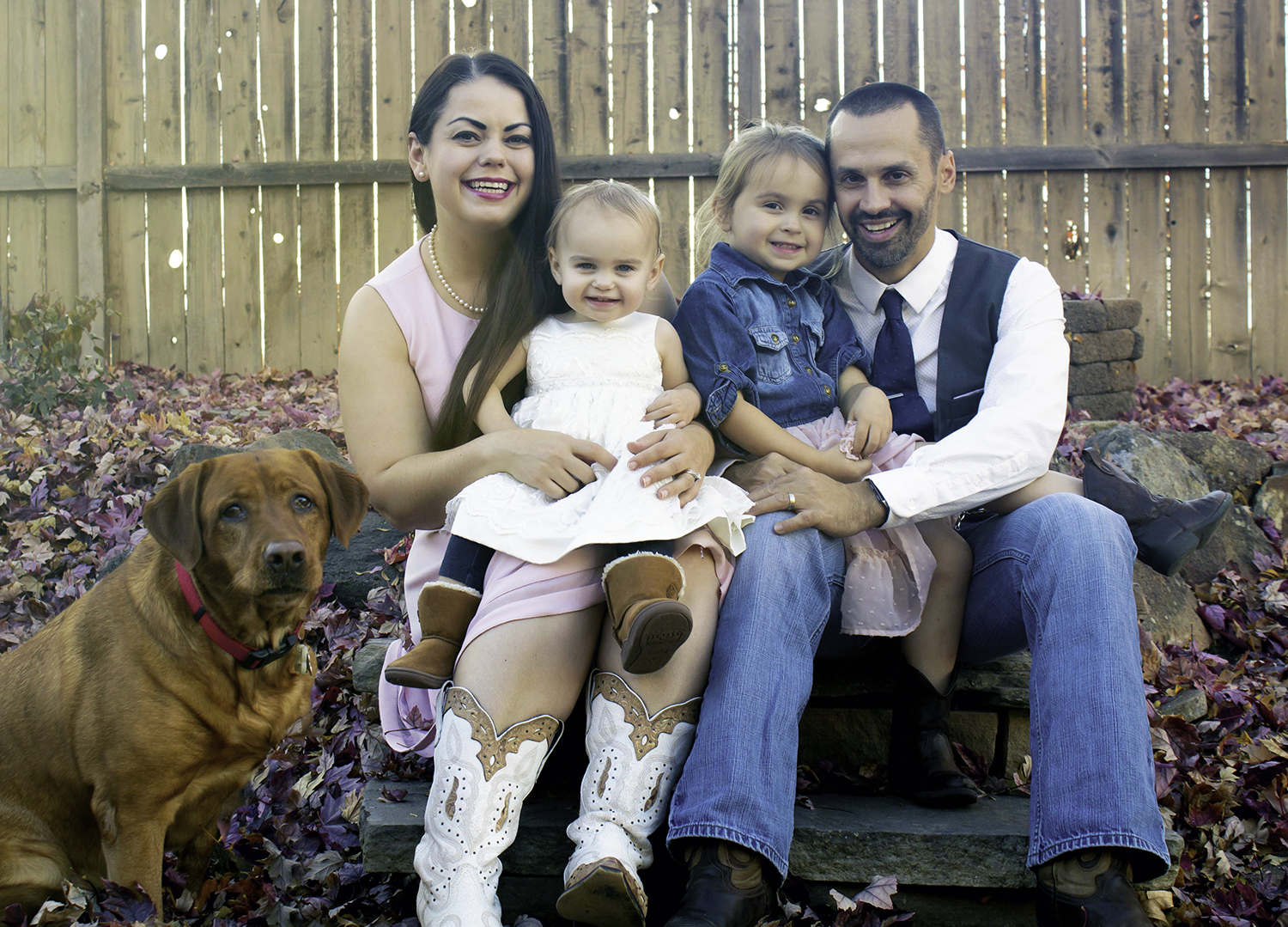 A mother, father, two daughters and a dog pose for the camera