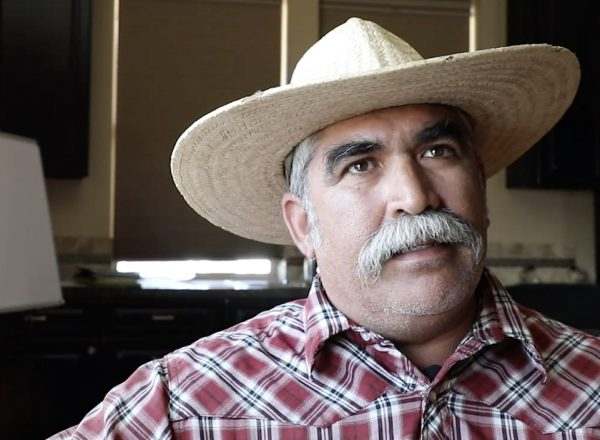 A man wearing a red shirt and straw hat talks to someone off camera