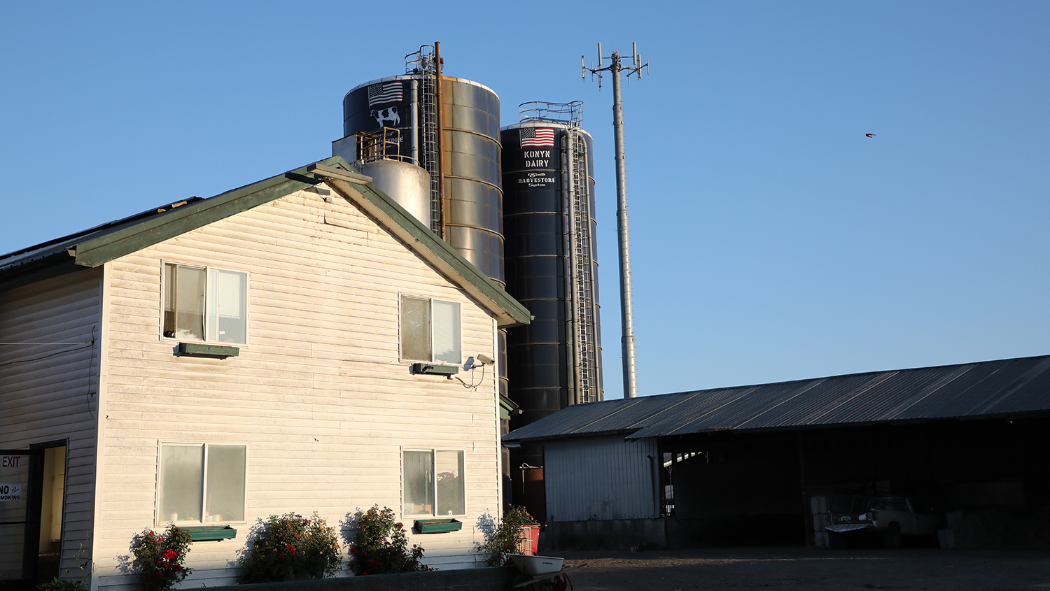 Photo of a farm house and silos at sunrise