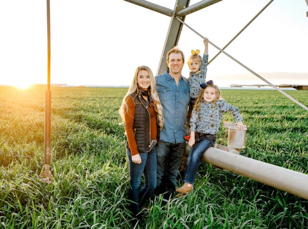 A family poses in a field at sunset