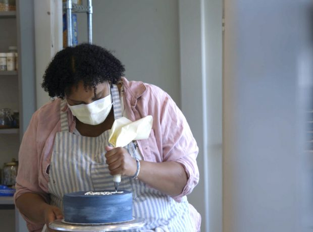 A black woman ices a cake