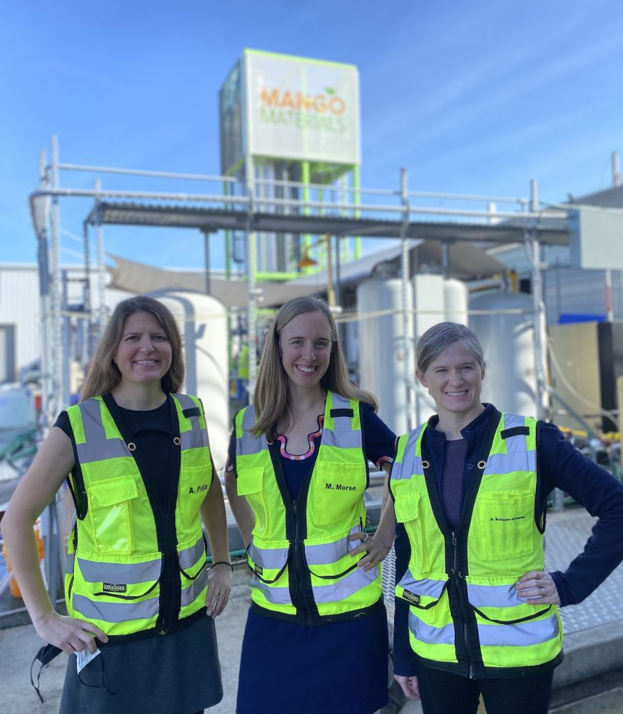 Three women in yellow jackets pose for the camera