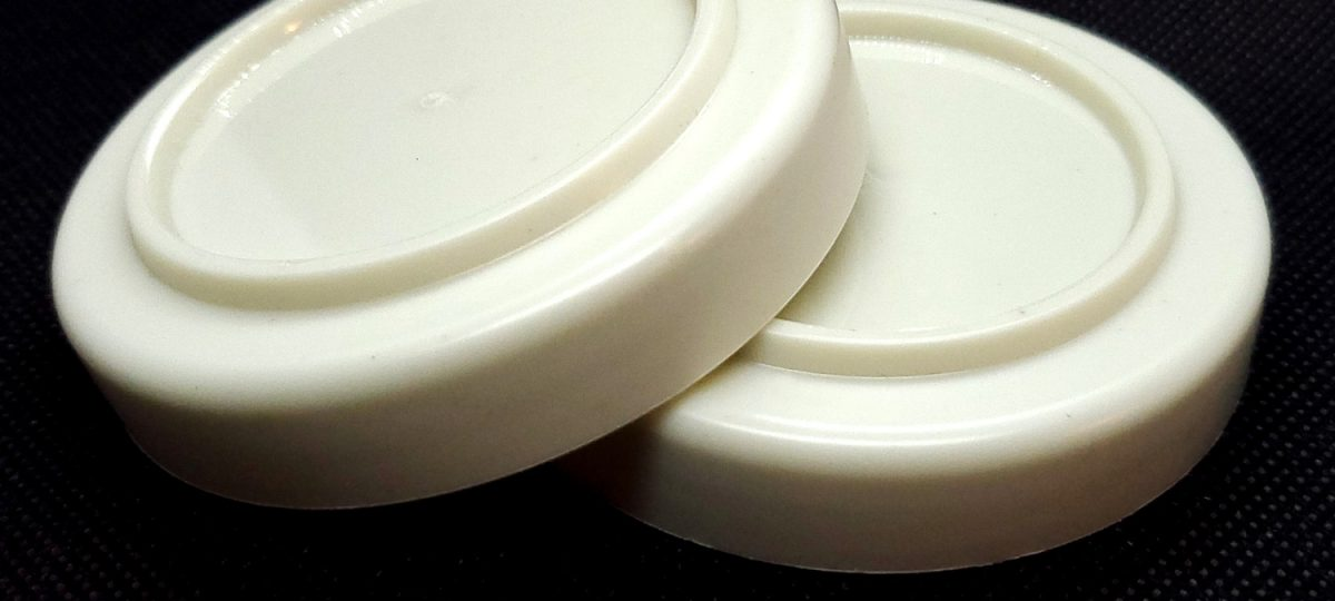 Two plastic caps against a black background