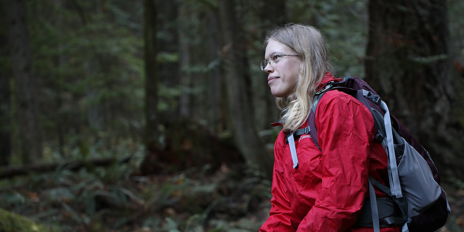 Woman in red jacket sits in a forest