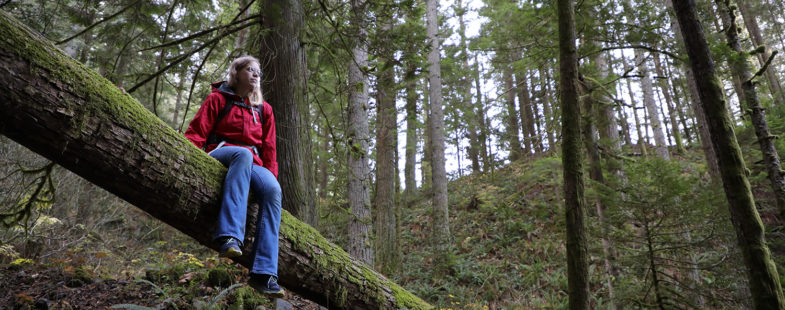 Woman in red jacket sitting on a log in the forest