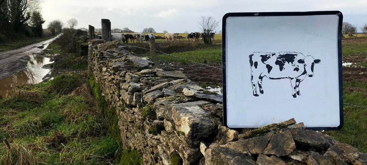 A painted Holstein cow on a sign in the English countryside