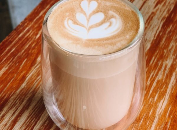 A cup of coffee on a wooden table with heart pattern in the froth