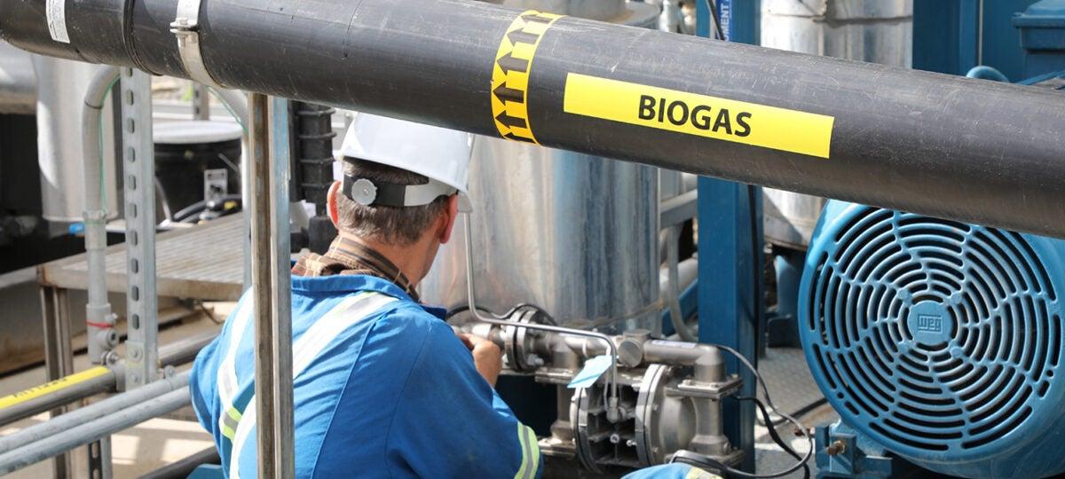Man wearing blue uniform working on biogas equipment