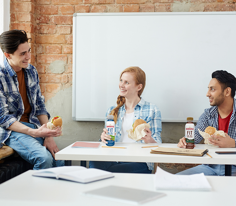 Three young people eating lunch in front of a whiteboard