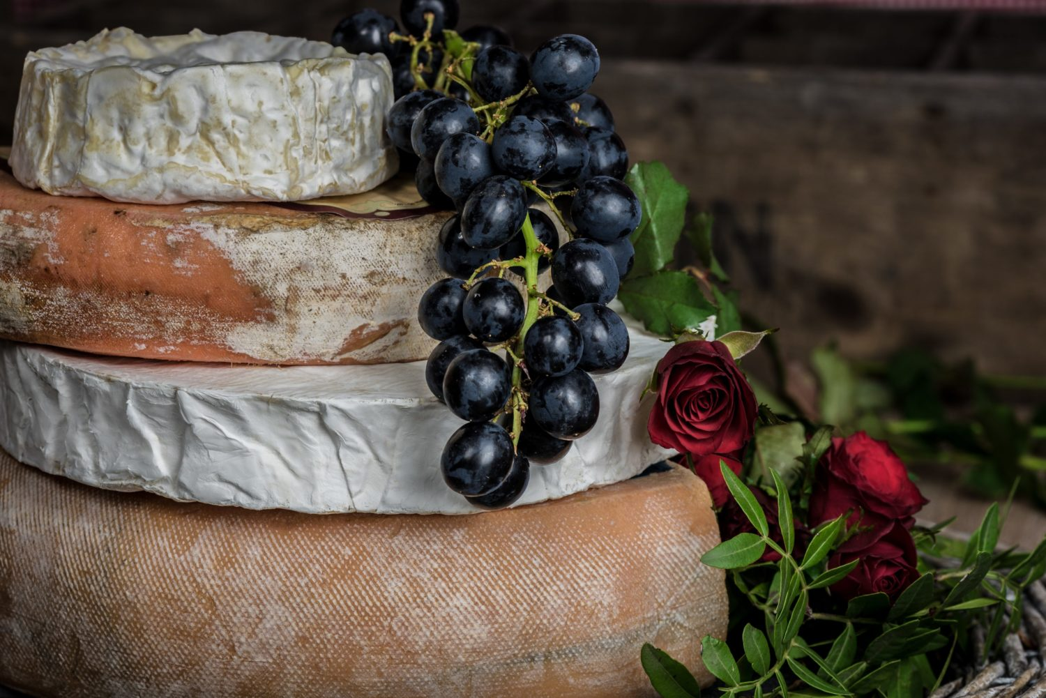 A stack of cheese with black grapes and a rose
