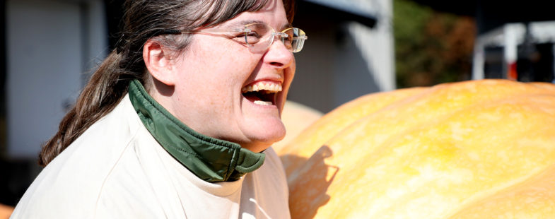 A woman laughing in front of a giant pumpkin