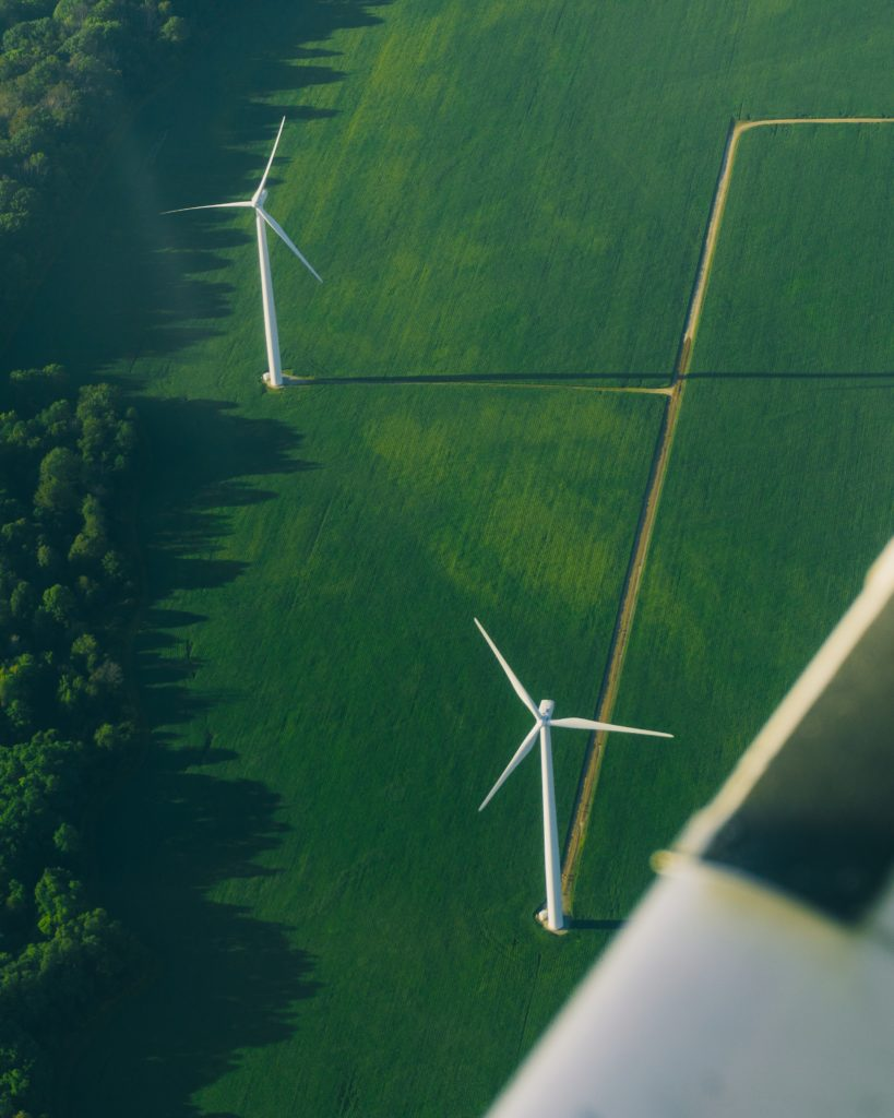 Aerial view of wind turbines in a grass field