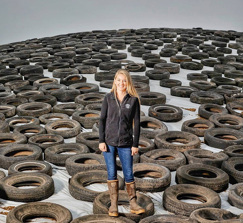 A woman stands on a mountain of recycled tires