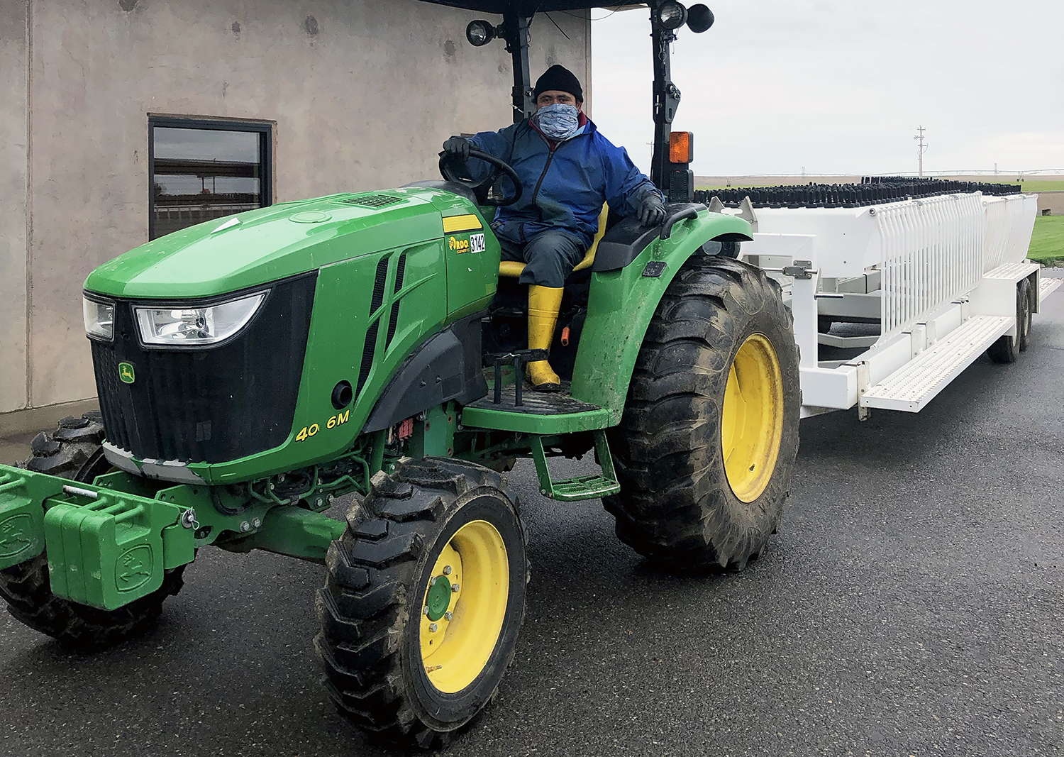 Hispanic man driving a green tractor with a trailer