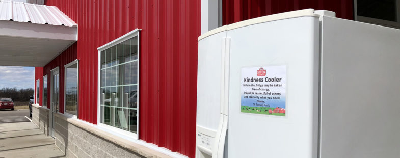A fridge stands outside a cherry-red building